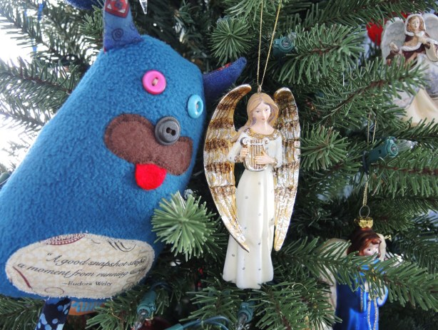 Edgar is sitting in a Christmas tree swooning over an angel Christmas ornament.  The angel is playing a lyre.