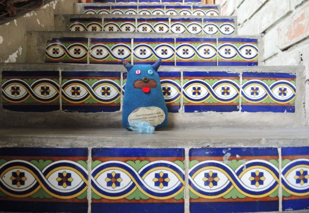 Edgar is sitting on the steps. The steps are concrete with blue and white tiles on the edges.