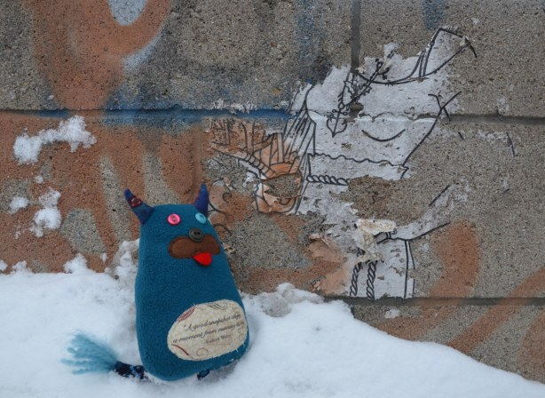 Edgar is standing on a snowbank. He is looking at a paper piece of graffiti that once was a woman but it is now torn so that only part of her body is visible