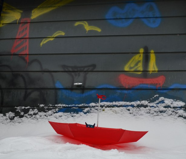 Edgar is in an upside down red umbrella in the snow, in front of a painting on a garage door.  The painting is of a red sailboat sailing beside a whale that is diving under the surface of blue water