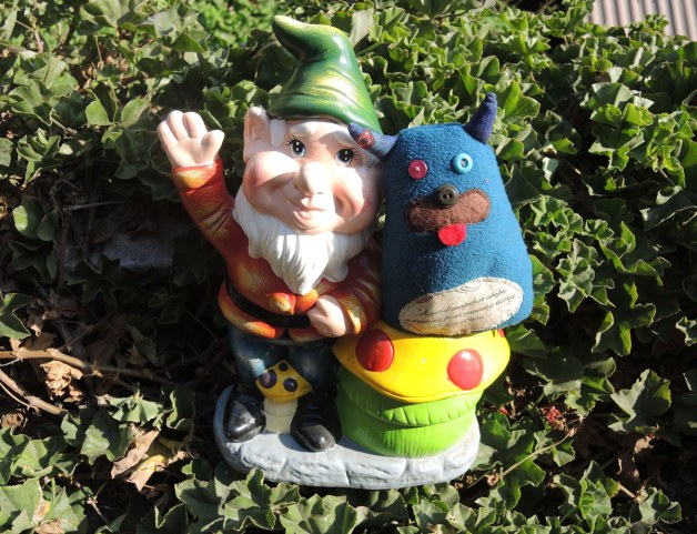 A ceramic garden gnome posing with Edgar.  The gnome is waving.  He has a white beard and he is wearing a green cap