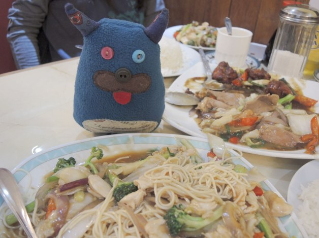 Edgar is sitting on a table in a Chinese restaurant. He is looking at a large plate of noodles and vegetables. A plate of duck with vegetables is beside him.