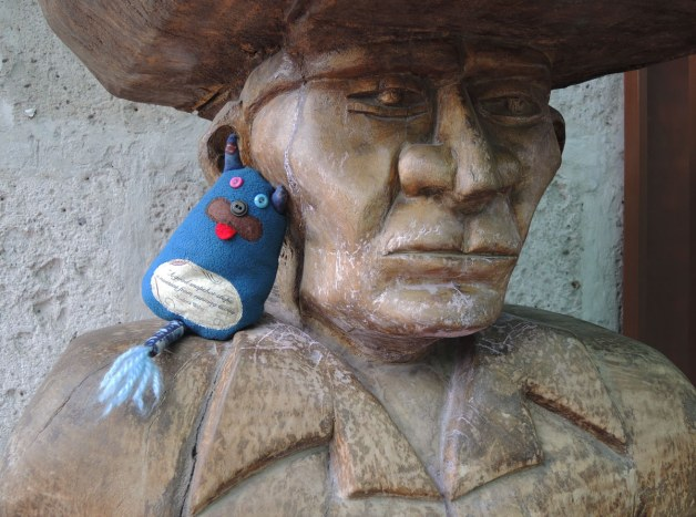 Edgar is sitting on the shoulder of a wood statue of a man with a hat on.