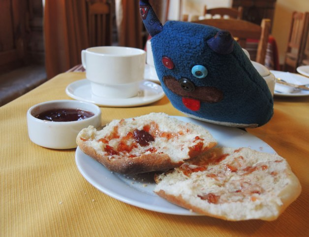 Edgar is leaning over, and looking at, a plate with a bun that has been cut in half.  There is strawberry jam spread on the bun.  It is on a white plate.  A small bowl of strawberry jam is beside him.