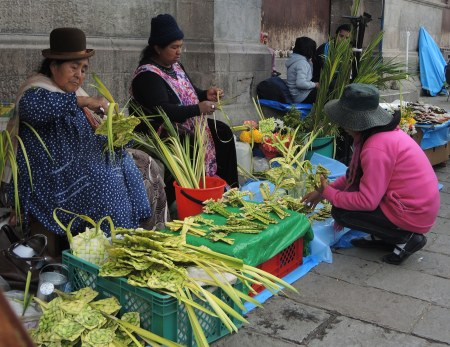 three women are making and selling palm crosses on the steps of a stone church.   They are dressed in traditional Bolivian clothes