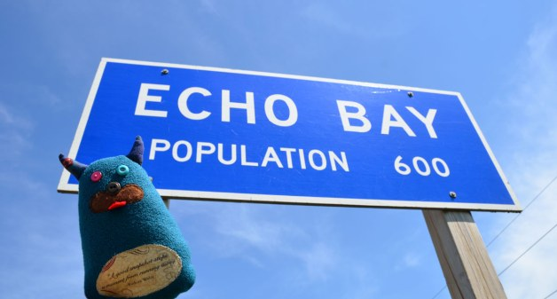 Edgar, the little blue monster is beside a blue and white sign that says Echo Bay Population 600