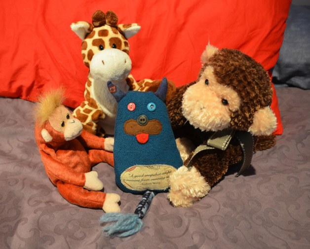 Edgar is sitting on a bed with three other stuffed animals, a large brown monkey, a brown and white giraffe and a small maroon coloured monkey.