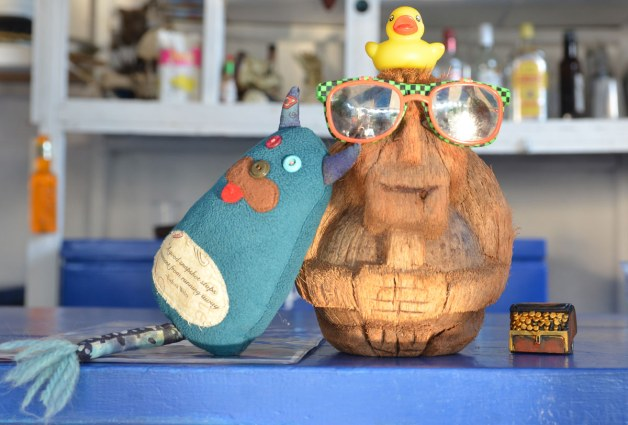 Edgar is sitting on a bar.  He is leaning against Coconut Joe, a character made from a cocnut shell who is wearing sunglasses.  A small yellow rubber duckie is sitting on Coconut Joe's head.