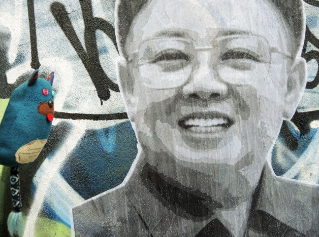 Edgar is beside a large paste-up graffiti or street art piece of the face of Kim Jung-il, former leader of North Korean who is now dead.