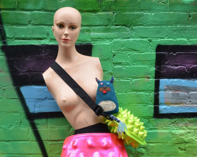 Edgar is with a mannequin that he met in an alley.  She is leaning against a green wall.  She has no hair, and no arms.  She is topless but is wearing a pink skirt and is carry a lime green shoulder bag.  Edgar is sitting on top of the green bag.
