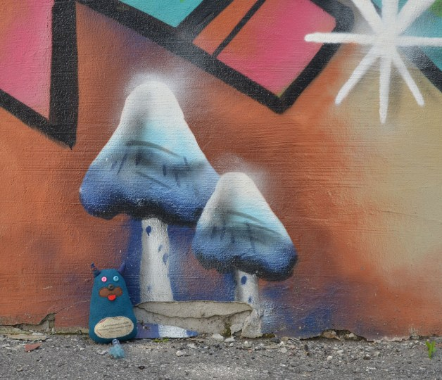 Edgar is standing in an alley.  It looks like he is standing under two greyish blue mushrooms or toadstools.... but they are actually painted on the wall behind him.