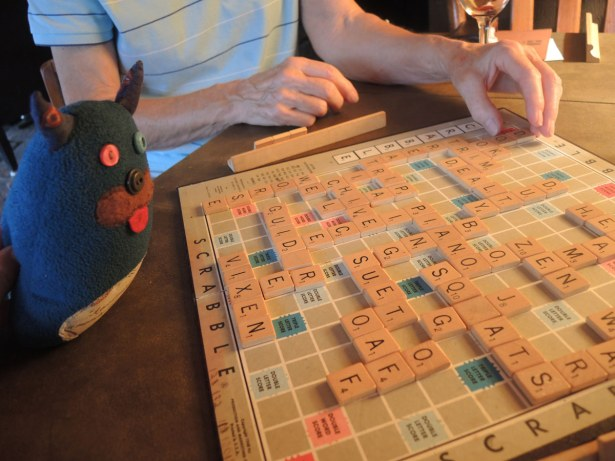 Edgar is looking at a scrabble board where the game is nearly over.  There are many words made on the board.