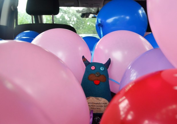 Edgar is the back of a hatchback car, surrounded by pink, blue and red balloons.