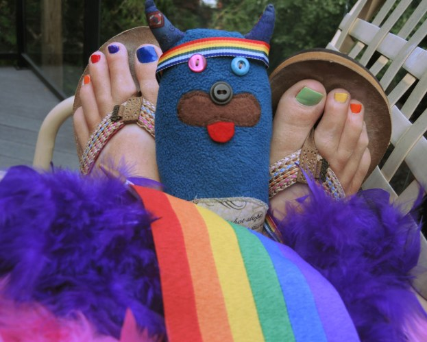 Edgar is sitting between two feet that have toenails painted in rainbow colours.  He is also sitting with a purple and a pink feathery boa as well as a small rainbow pride flag.