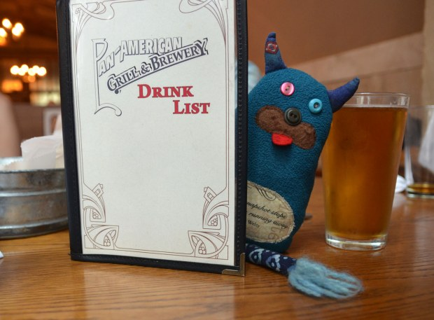 Edgar is peeking out from behind a drinks menu at a bar.  He is on the table along with a full glass of beer.