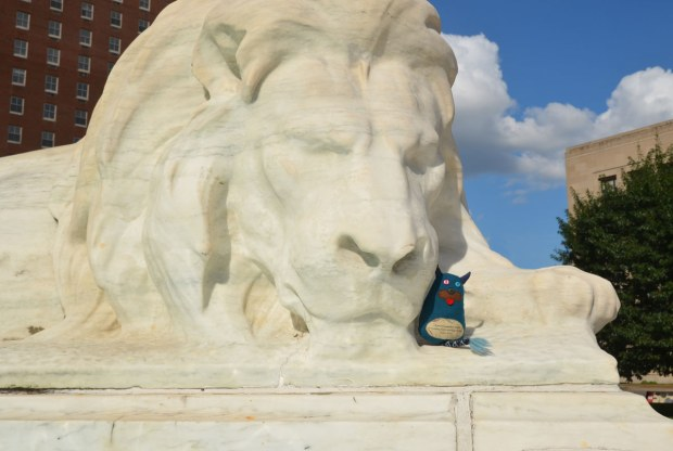 Edgar is cuddled up next to the cheek of a white marble lion who is lying beside a fountain. The marble is badly eroded.