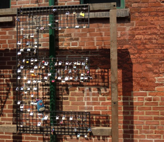 A large wire mesh letter E is attached to a brick wall.  On the E people have put padlocks.  Edgar is sitting in one of the corners of the E.  Distillery District in Toronto