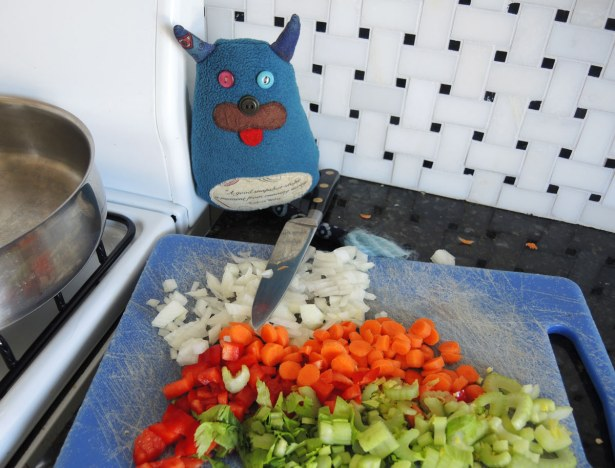 Edgar is sitting on the kitchen counter with a large knife.  In front of him is a cutting board with chopped carrots, celery, red pepper and onions.