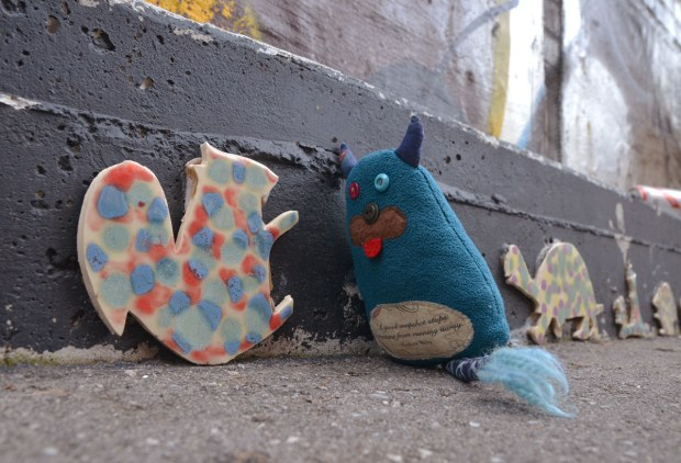 Edgar is standing in an alley.  He is talking to a red and blue spotted cut out in the shape of a squirrel that is about the same size that he is.  A turtle is against the wall behind him and there are a couple of animal shapes in a line behind the turtle.