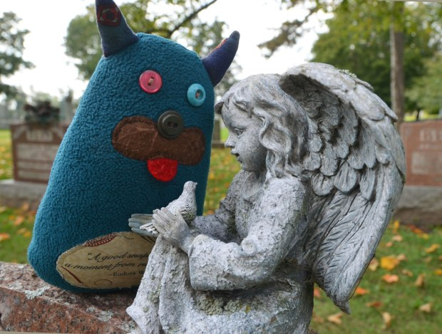 Edgar is sitting beside a little stone angel who is holding a dove in her hands.  They are  on top of a tombstone in a cemetery.
