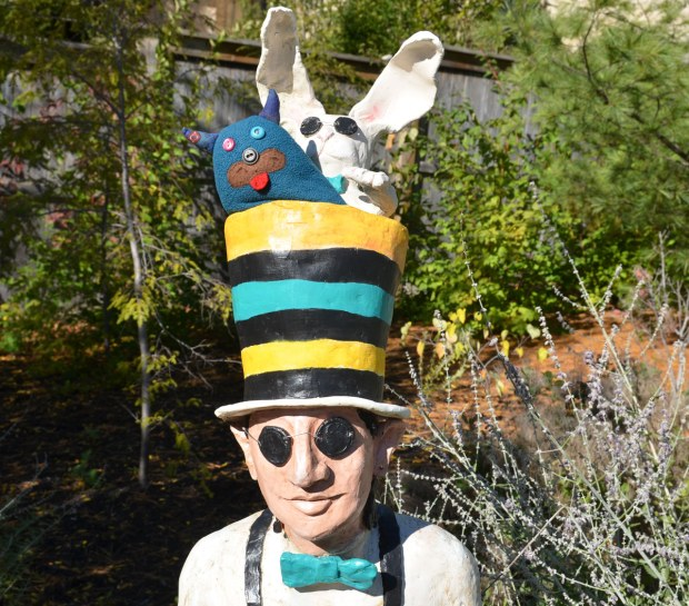 Edgar is looking out over the top of a large black, yellow and blue striped top hat. A white rabbit wearing sunglasses is beside him. The hat is on the head of a short man who is also wearing sunglasses. The man and the rabbit are a statue in a park.