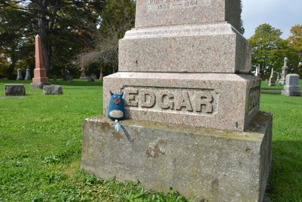 Edgar is sitting on the base of a large stone monument in a cemetery. The surname inscribed in the tombstone is Edgar.