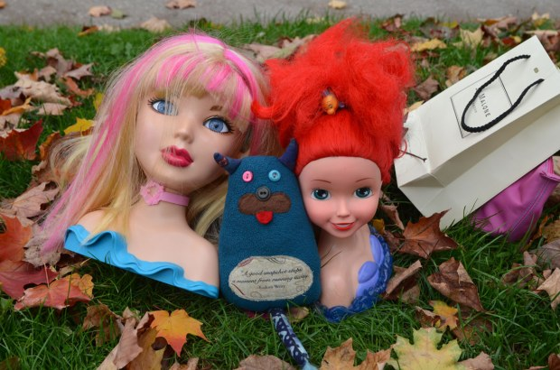 Edgar is sitting between two heads.  One is make-up barbie and the other is Ariel, the little mermaid.  Both of them are bigger than Edgar.  They are on the ground (grass) beside a sidewalk