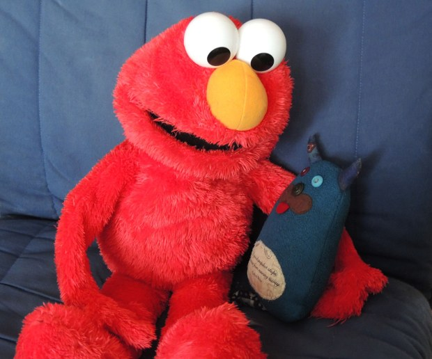 Edgar is sitting on a blue chair.  He is sitting with a large Elmo who has his arm around Edgar.
