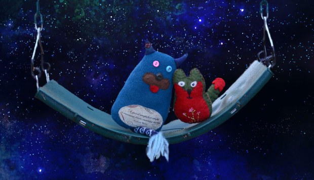 Edgar and Flora are sitting on a swing.  The backdrop is a painting of a dark blue starry night