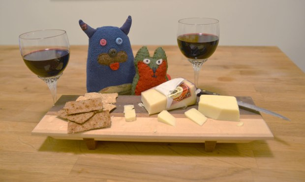 Edgar and Flora are sitting behind a cheese board that has a couple of kinds of cheese on it as well as some crackers.  Two glasses of red wine are on the table too.
