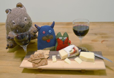 Edgar and Flora are sitting behind a cheese board that has a couple of kinds of cheese on it as well as some crackers.  Two glasses of red wine are on the table too.  Wombie, the stuffed wombat is drinking from one of the glasses.
