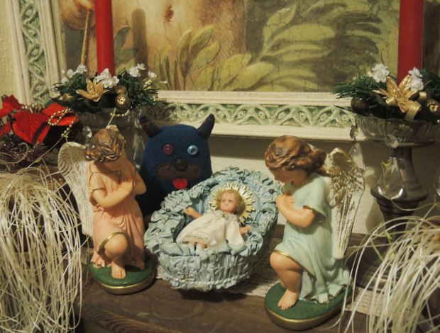 Edgar is standing beside a little ceramic nativity scene.  Baby Jesus is in the manger and two angels are on either side of him.   There are red candles decorated with fake pine and poinsettia