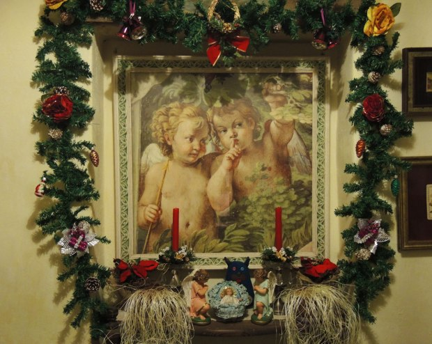 Edgar is standing beside a little ceramic nativity scene.  Baby Jesus is in the manger and two angels are on either side of him.   There are red candles decorated with fake pine and poinsettia.  Above them is a large picture of two little angels in a garden.