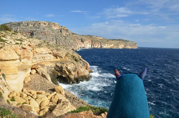 Edgar has his back turned to the camera as he looks out over the blue Mediterannean Sea and the rocks and cliffs along the shore.