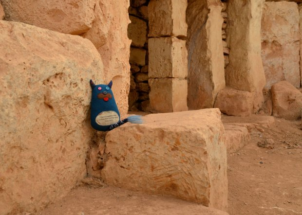 Edgar is sitting on a large limestone block that is part of a neolithic structure. A few stone columns can be seen behind him.