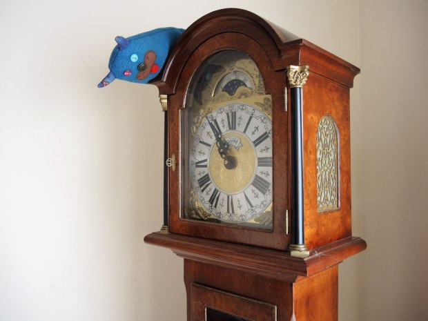 Edgar is sitting on top of a small grandfather clock and he is looking down at the face of the clock.