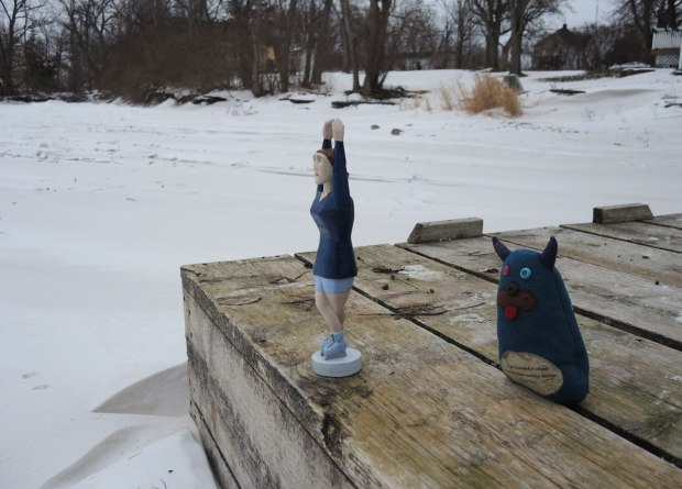 Edgar is standing back from the edge of a dock, keeping an eye on Sonya who is a figure skating figurine with her hands over her head, looking like she is ready to dive.
