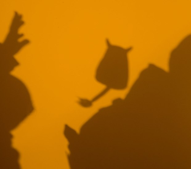 Dark brown shadows on a yellowish gold coloured background.  On the left is an open hand, in the middle is Edgar and on the right is a backpack.  Edgar has been thrown towards the backpack and has been caught in mid air.