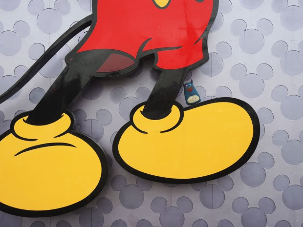 Edgar is standing on a yellow foot of a vary large picture of Mickey Mouse.  Only the bottom part of Mickey is visible, from the bottom yellow button of his red shorts down.