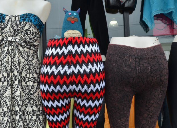 Edgar is standing on top of a half mannequin, the lower half of a mannequin that is wearing zig zag striped red, black and white leggings.