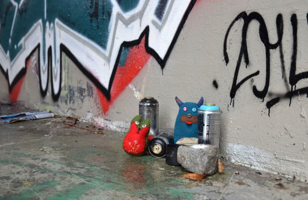 Edgar and Flora are beside a concrete pillar under a bridge.  They have some cans of spray paint with them.  There is graffiti on the wall beside them.