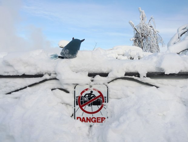 Edgar is standing on top of a snow and ice covered wrought iron fence at Niagara Falls.  There is so much snow you can hardly see the fence.  Some snow has been cleared away to reveal a danger sign that has a picture on it meaning don't climb on or over the fence