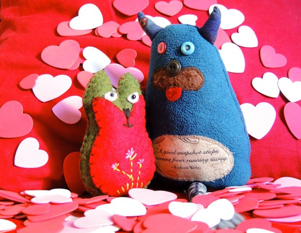 Edgar and Flora are on a red cushion surrounded by many little red, pink and white heart shaped pieces of flat foamy craft stuff.