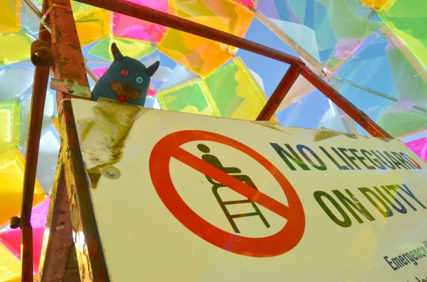 Edgar is sitting on a lifeguard chair, just on top of the sign that says No Lifeguard on Duty.  The chair is surrounded by an art installation called Snowcone, numerous translucent geometric shaped pieces of plastic that let the sunlight in.   Bright colours.