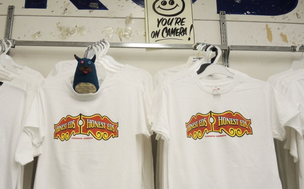 "Edgar is tucked into the neck of the front T-shirt in a rack of many.  They are white men's T-shirts with a picture of Honest Ed's storefront sign.  The words ""Toronto Canada"" are also written on the T-shirts.  Above the rack of T-shirts is a happy face sign letting the viewer know that they are on camera."