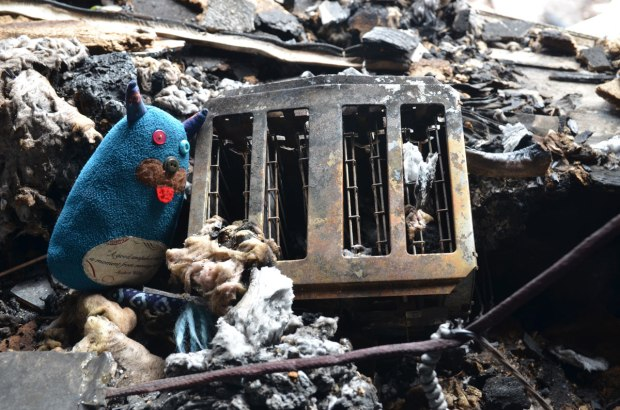 Edgar is sitting on a pile of burnt debris beside a toaster that has also been in the fire.  Everything is charred and dirty.