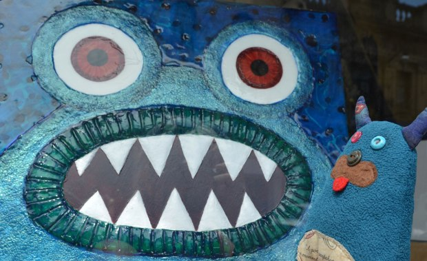 little Edgar found a picture of blue monster face in a gallery window. The painting has big round red eyes and sharp pointy teeth. The title of the painting is 'We need monsters number five'