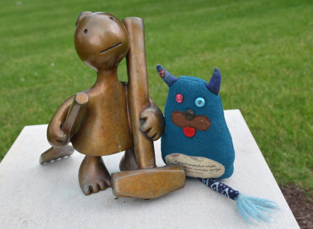 Edgar is standing beside a llittle bronze figure who is holding a hammer in her hand.