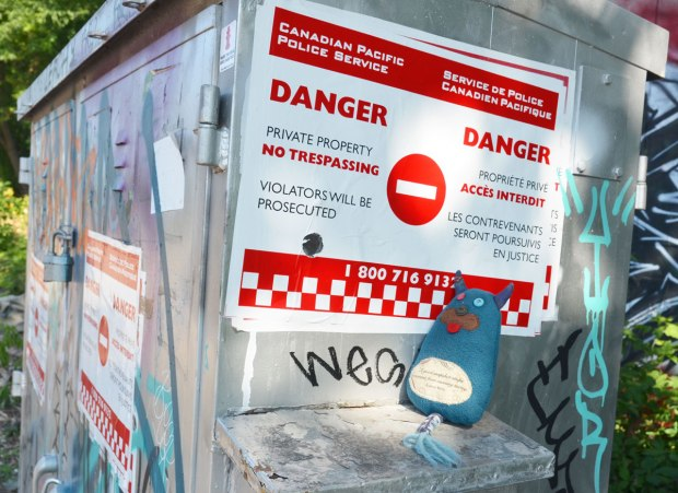Edgar is standing beside a red and white sign that says Danger, private property, no trespassing, violators will be prosecuted, (and also in French)posted by the Canadian Pacific Police Service