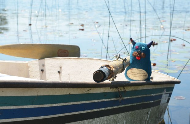 Edgar is sitting on the edge of a rowboat, and is beside one of the oars.